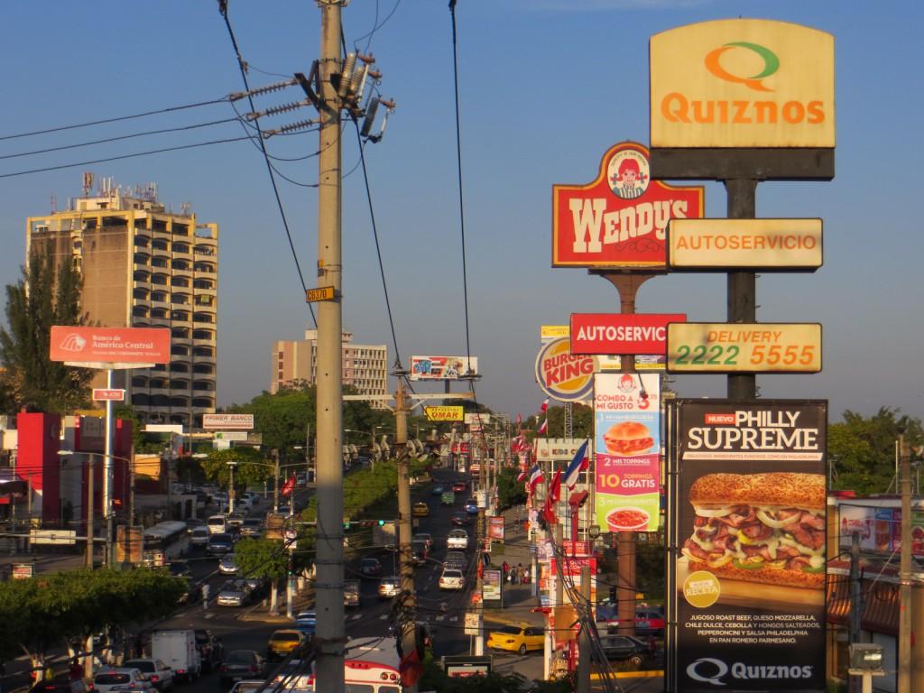 Dit is een typische plaatje van San Salvador. Drukke wegen, chaotisch, vies, maar ook kleurrijk door de reclame van de vele ketens.