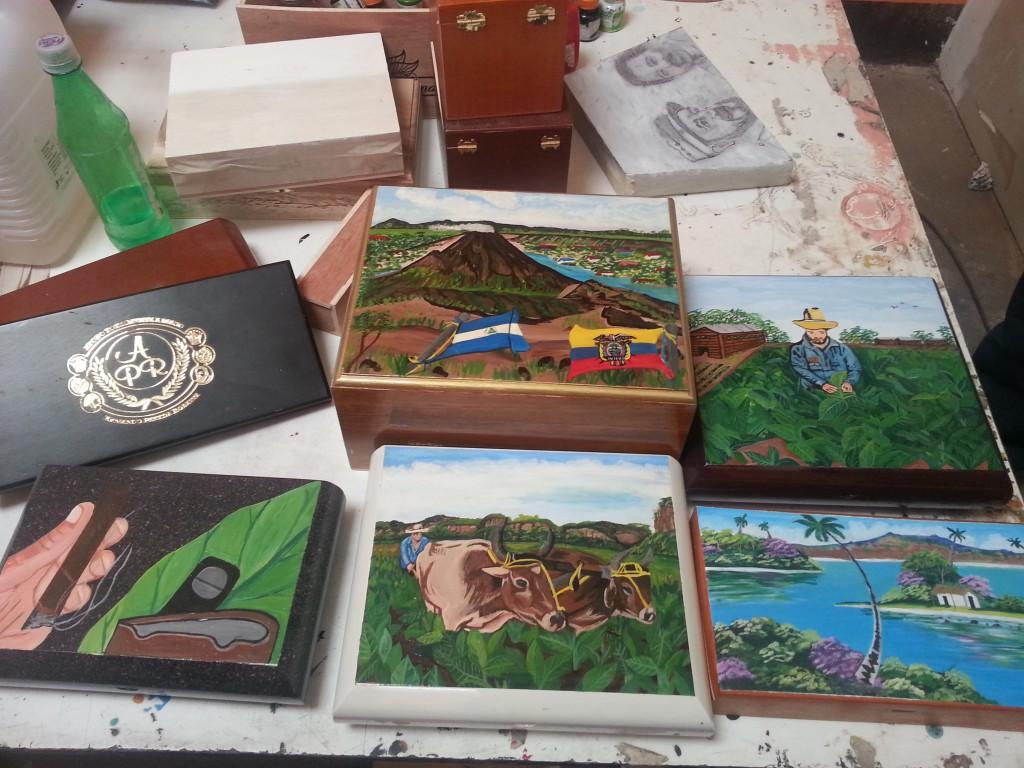 De kleurrijke handgeschilderde sigarenkistjes. Kijk ook naar het ontwerp van Fidel Castro dat klaar ligt.