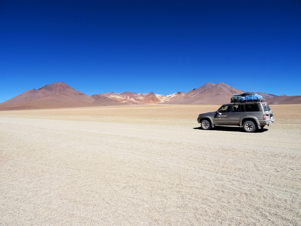 Dit was een typisch beeld voor de vier dagen die we in en om Uyuni doorbrachten. De jeep, de vlaktes en de kleurrijke heuvels op de achtergrond.